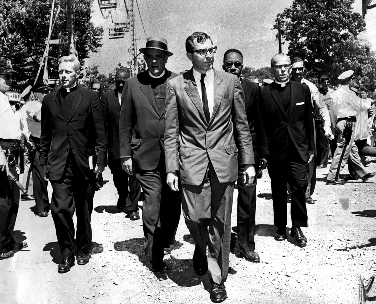 These clergymen of varied faiths head for a patrol wagon at Gwynn Oak Park during yesterday's anti-segregation demonstrations include the Rev. Joseph M. Connolly (left), of the Catholic Interracial Council, the Rev. Dr. Eugene Carson Blake (second from left), stated clerk of the United Presbyterian Church, and the Rev. Marion C. Bascom (fourth from left), pastor of Douglas Memorial Church. More than 250 persons were arrested at the amusement park. Photo by Clarence B. Garrett/1963 file photo