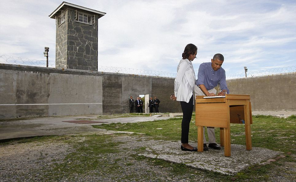 U.S. President Obama writes in a guest book as he tours Robben Island near Cape Town