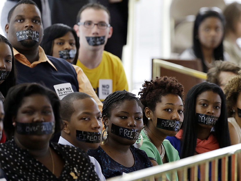 Members of North Carolina student chapters of the NAACP and opponents of voter ID legislation wear tape over their mouths while sitting silently in the gallery of the House chamber of the North Carolina General Assembly where lawmakers debated and voted on voter identification legislation in Raleigh, N.C., Wednesday, April 24, 2013. (AP Photo/Gerry Broome)