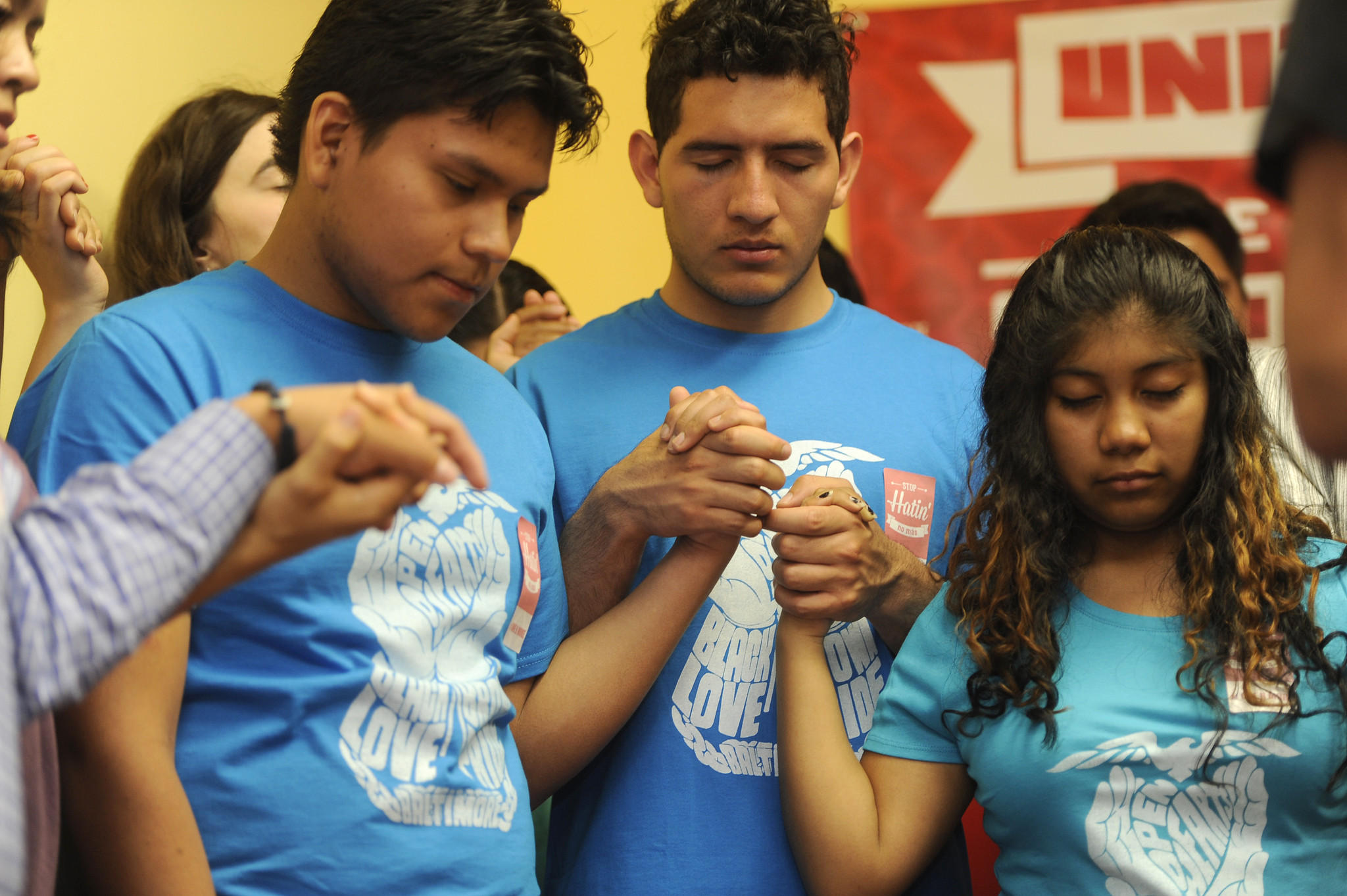 Left to right, praying at the end of a press conference: Jose Dominguez, Edwin Vasquez, Yanderi Hernandez. Representatives from hispanic and African American communities held a press conference at CASA de Maryland regarding ideas to prevent violence between the two communities. (Barbara Haddock Taylor, Baltimore Sun)